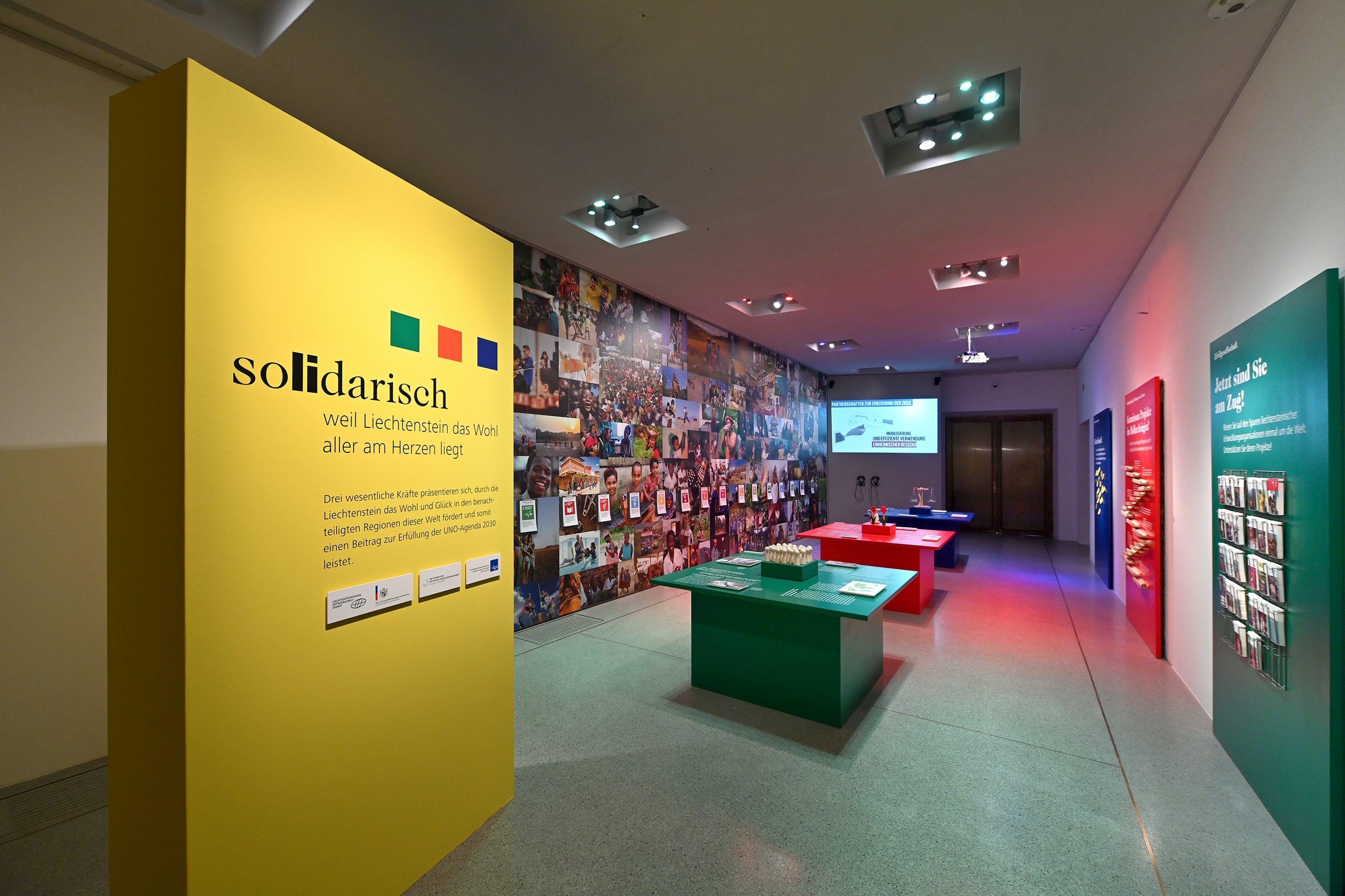 """Blick in die Ausstellung """"Global Happiness"""" mit Zusatzausstellung «solidarisch – weil Liechtenstein das Wohl aller am Herzen liegt»"""
